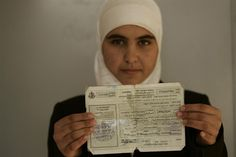 "Hanadi (age 15) holds her identification card, required in the 'Seam Zone' between the Israeli barrier wall and the West Bank's internationally-recognized border with the Occupied Palestinian Territory. Residents of the zone need special permits and are often detained at military checkpoints. Children must also pass a checkpoint to go to school. ""I feel like I'm in prison,"" said Hanadi.  - 2007 ©UNICEF/ Kate Brooks - http://www.unicef.org/photography"