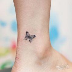eine kleine tolle schwarze mini winzige tätowierung mit einem schönen schwarzen fliegenden schmetterling auf bein