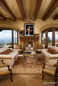 In contrast with the entryway, which is southern Italian in influence, the living room embraces northern aesthetics through the use of stripes, a more specific color sense, and symmetry. The stone fireplace was crafted by Richard Young; the hand-carved inset is from Visions' workshop and serves as a centerpiece in the room. Putting the Chinese pots in the summer months adds a sense of focus to an otherwise vacant space. The coffee table is burnished silver leaf with a travertine inset.