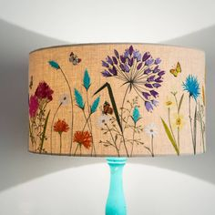 Embroidered onto 100% linen, with bright shots of floral colour, this statement lampshade will bring summer and light in to your home!This lampshade comes in a off-white 100% linen. If you require a different coloured base fabric to fit in with your home, please feel free to ask. My lampshades are all made-to order, so colour variatons are possible.This stunning lampshade is suitable for sitting room, bedroom and any dark corners in your home needing some artisitic illumination. This…