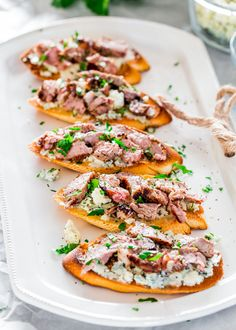 These blue cheese and steak crostini are a perfect addition to your holiday party or game day menu. Delicious grilled steak pieces over blue cheese and topped with a balsamic reduction, utterly scrumptious!