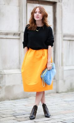 Springtime sweaters done right. Yellow midi skirt, baby blue clutch, a delicate gold necklace and chic black heels