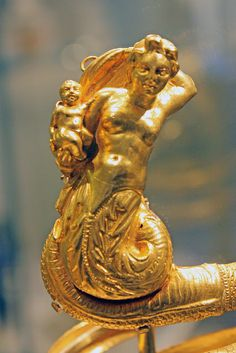 Pair of gold armbandsPeriod:    HellenisticDate:    ca. 200 B.C.Culture:    Greek These imposing serpentine armbands represent two tritons,male and female,each holding a small winged Eros.
