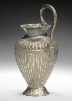 An East Greek silver oinochoe  Late 6th-5th century B.C. With flared neck, the high arched handle with palmette terminals, the ovoid body decorated with tongues on the shoulder, with corresponding fluting beneath, set on a flared foot decorated with a band of tongue motifs with a rosette on the base, 4in (10cm) high