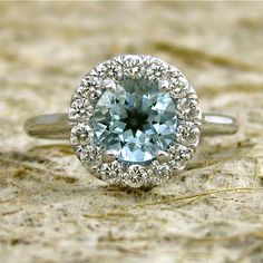 Elegant Classic Halo-Style Aquamarine & Diamond Engagement Ring in 14K   The Round Aqua weighs 1ct. , and is 6.5 mm.  Diamonds have a total carat weight of approx. 0.50cts. Diamonds are F Colour, VS Clarity. Stones could be set on the shank, if needed. The halo-style setting is cast in 14k White Gold.