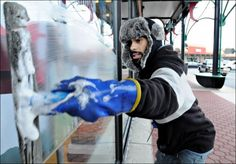 Edgardo Gomez of Triple D Window Cleaning races along and tries to keep warm while cleaning store front windows at the Doylestown Shopping Center