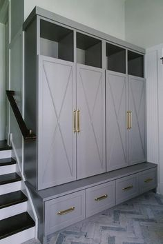 Gorgeous gray sunken mudroom boasts a gray herringbone floor leading to gray x-front close locker doors accented with brass handles and positioned below overhead shelves and above a gray storage bench.