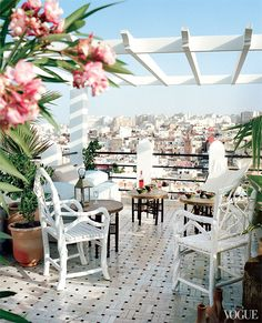 a comfortable and practical seating area around Moroccan- style tables under the pergola with the view of the city of Tangier, Morocco