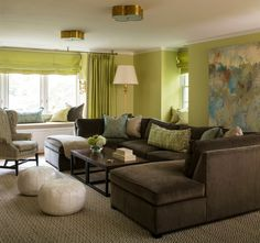 Green and brown living room features walls painted green lined with a a large gray and blue abstract art piece hanging over a deep brown velvet sectional in U formation lined with turquoise and green pillows facing side by side industrial coffee tables as well as two white leather Moroccan poufs illuminated by Basil Flush Mounts.