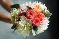Coral roses make a lovely statement in this white bridal bouquet. | Gumina's Flowers in Grand Rapids, MI