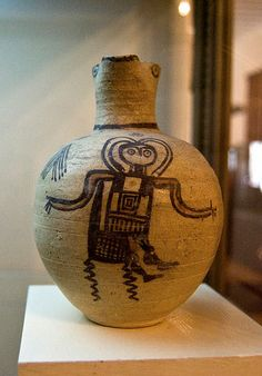 ancient art -  this vace  shows a being wearing a suit that appears to include a helmet and controls on the front - the subject is sitting on something, and the legs of that object suggest movement.