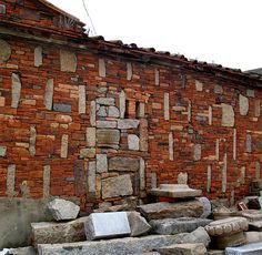 Picture of brick and stone wall built from remains of demolished building in ancient city.