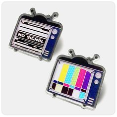 A pair of fritz-y, glitch-y, retro TV pins by Coey Kuhn. High-quality printed and coated with epoxy, this pair of old tubes might not get signal, but will outlast their era with how sturdy they are…