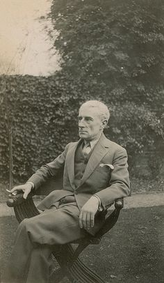 Maurice Ravel having a smoke in a chair in the garden.