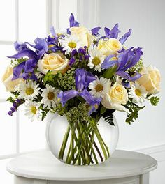 Spring Flowers - FTD Sweet Beginnings Bouquet - PREMIUM - The FTD Sweet Beginnings Bouquet exudes the promise of each day's potential with its unlimited beauty. Deep purple iris mingles with pale yellow roses, white traditional daisies, Queen Anne's Lace and lush greens to create an incredible look. Arranged in a clear glass bubble bowl vase, this bouquet is full of warm wishes and sweet sentiments.