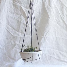 These hanging planters are thrown on the wheel with a rolled rim to simplify how the planters hang. Each planter comes with cord and a porcelain ring for easy install. Drainage hole in base. Approx. 6 wide and 3 tall Torrent is shown in the first and second photo. Crater is shown in the