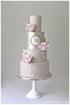 Wedding cake of piped swiss dots & blush sugar roses with bespoke painted monogram. Gilded details and champagne lustre.