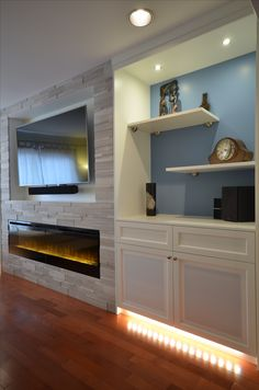 Custom #fireplace wall with TV. @erthcoverings Silver Fox strips, @dimplex BLF74 electric fireplace, custom cabinetry with AV storage and display space.