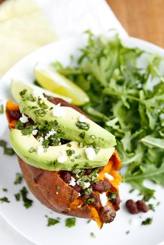 Baked Sweet Potato -- these loaded baked sweet potatoes, topped with honey-lime chipotle black beans, sliced avocado, crumbled queso fresco, and chopped fresh cilantro, are a  fantastic meatless meal solution! One of our fave Lent recipes...