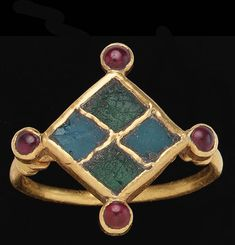 Medieval Merovingian finger ring, gold, glass and garnet, circa 5th-6th Century A.d. The hoop round in section, with collared shoulders joined to the diamond-shaped bezel, which is divided into quadrants and set with alternating squares of blue and green glass, the corners of the bezel terminating in roundels set with cabochon garnets
