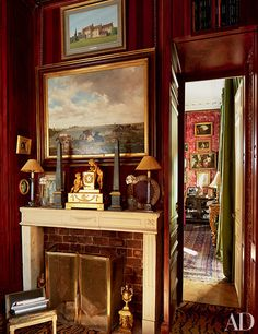 An Empire clock and a pair of obelisks top the mantel in the faux-mahogany library of a Paris apartment.