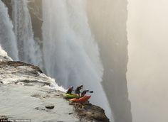 Daredevil kayakers Steve Fisher, Dale Jardine and Sam Drevo paddled up to the lip of the mile-wide Victoria Falls which flows between Zambia and Zimbabwe. They are standing on one of the islands that appear during the dry season looking over the 350 ft drop of water while crocodiles lurk nearby.