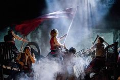 Les Miserables- Enjolras waving the flag in the fog. And Grantaire reaching for him is a lovely touch! This is such an epic, tear-jerking moment!