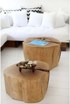 Logs as the coffee table and simple bowl with stones in a white room with a white sofa.  Clean!
