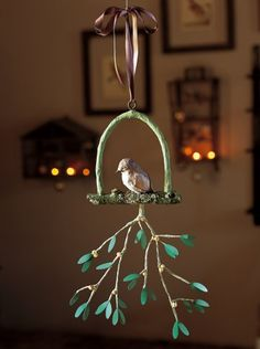 A branch + some wire + a few pieces of newspaper = A whimsical bird on a swing holding a sprig of mistletoe... just waiting for you & your Prince Charming to walk under!