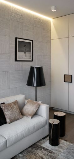 TV Room beautifully layered with cow skin rug and cushions and textured wall-covering. Stumps from Gervasoni.