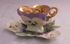 Heart shape Tea cup, gold inside, lavander and white decorated with small flowers, also the handle i so beautiful.  I want it,