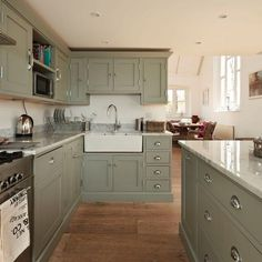 Sage-green kitchen cabinets look terrific against a beige ceiling. This is a color (Greyhound 1579 from Benjamin Moore. Sage Green Kitchen, Green Kitchen Cabinets, Custom Kitchen Cabinets, Painting Kitchen Cabinets, Kitchen Paint, Home Decor Kitchen, New Kitchen, Kitchen Grey, Kitchen Ideas