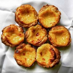 Seven pastéis de nata--Portuguese custard pastries with flakey shells filled with a mottled burnt surface Portuguese Custard Tart Recipe, Portuguese Tarts, Portuguese Recipes, Portuguese Food, Tart Recipes, Wine Recipes, Sweet Recipes, Natas Recipe, Baked Egg Custard