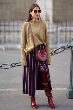 A guest wears an oversize pull over a red circular bag a striped skirt red boots outside the Dries Van Noten show during Paris Fashion Week...