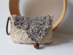 This crocheted bag is perfect for summer outfits. It is small but comfortable, thanks to its wristlet handle and crocheted asymmetric flap,