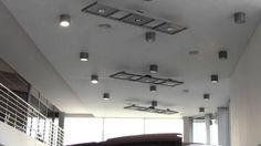 W salonie samochodowym wykonany został biały sufit napinany, w którym umieszczono różne oprawy oświetleniowe.