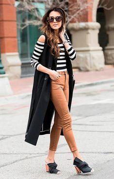 Christine Andrew posa para foto usando blusa de ombros à mostra de listras, colete longo preto, calça skinny de cintura alta caramelo, óculos escuros e mule proenza schouler