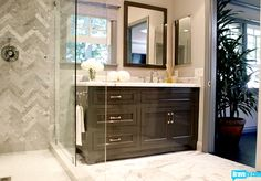 Herringbone marble tile pattern at shower, offset sink with window/mirror. Jeff Lewis Interior Therapy
