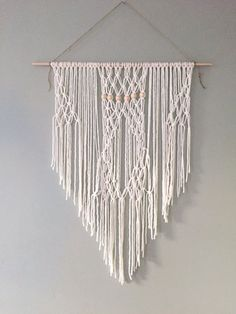 Cotton macrame wall hanging with wooden beads. Wood bar is 29 wide, cotton hangs 36