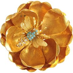 Vintage Hattie Carnegie goldtone dimensional flower with a bee covered in faux turquoise and white rhinestones. The pin is marked 'Hattie Carnegie'.   $135