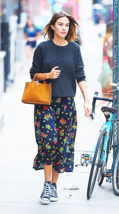 Alexa Chung wears a sweater, floral midi skirt, suede mini tote, and high top sneakers
