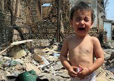 Плачущий ребенок у разрушенного дома в Цхинвале.