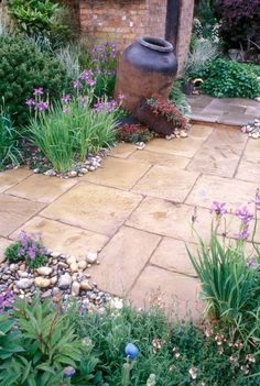 Stone patio with rustic urn, irises, spring flowering plants