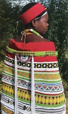 Africa | Woman wearing a beautiful beaded cape.  ca. 1970s | Although the source indicates that this is a Zulu woman, this cape is dominated by non-Zulu colours, that might suggest that it is a Ntwane woman