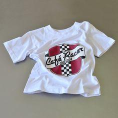 Camiseta infantil unisex en color blanco. Logo: Escudo Café Racer Obsession. Tejido de punto fino. Composición: 1OO% algodón hilado en anillos.