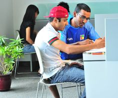 A student learns from his peer tutor in the Centennial College Learning Centre at Progress campus