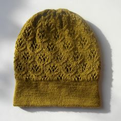 A lace patterned beanie type hat with ribbed brim knitted in fingerweight yarn. When knitted longer can become a slouchy hat. Textured pattern resembles orchard on the hill.
