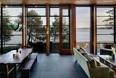 This says indoor outdoor room to me, more forest than sea.  Loving the dark tiles against the wood with lots of natural light.  Almost a sophisticated cabin.