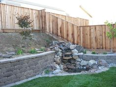 Water feature integrated into retaining wall, though the wall should be made with more natural rocks to tie it all together.