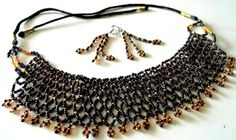 Look stylish in this lovely bead choker and danglers set from Gujarat. The choker has a thread cord that can be tied behind the neck. A designer creation from India's villages.  - See more at: http://giftpiper.com/HandmadeBeadChokerSet-Black-GoldBeads-id-590903.html#sthash.QD7HWAra.dpuf